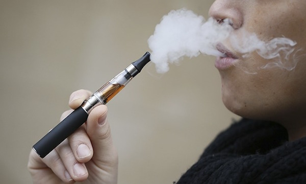 A person smokes a refillable electronic cigarette